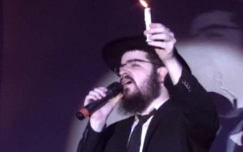Benny Friedman holding a candle, singing don't let the light go out