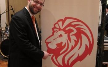 Ari B standing next to the NEW Nusach Ari logo/banner